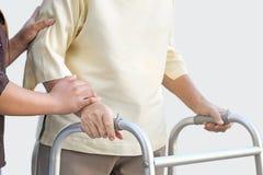 Donna senior che usando un camminatore con il badante Immagine Stock