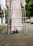 Donna senior che usando un camminatore sulla via Immagine Stock Libera da Diritti