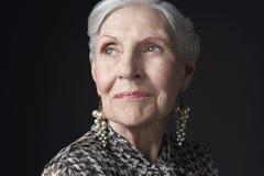 Donna senior con cercare degli orecchini della perla Fotografie Stock Libere da Diritti