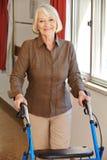 Donna senior con il camminatore nel resto Immagini Stock