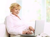 Donna senior con il computer portatile. Fotografia Stock