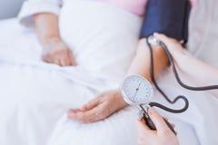 Donna senior con il monitor di pressione sanguigna sul suo braccio fotografia stock