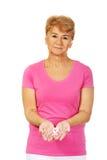 Donna senior con il nastro di consapevolezza del cancro al seno immagini stock libere da diritti