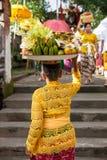 Donna senior con il piatto pieno dei frutti sulla testa immagine stock libera da diritti