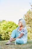 Donna senior con il piede storto in parco con dolore fotografia stock libera da diritti