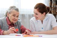 Donna senior con il suo infermiere più anziano di cura immagine stock