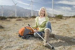 Donna senior con l'escursione Palo e dello zaino al parco eolico Fotografia Stock