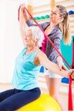 Donna senior con la banda di allungamento a forma fisica Fotografie Stock