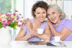 Donna senior con la figlia con la rivista Immagine Stock