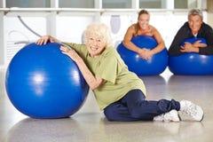 Donna senior con la palla della palestra nel centro di riabilitazione Immagine Stock