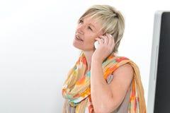 Donna senior dei bei capelli biondi che lavora all'ufficio con il telefono a Fotografie Stock