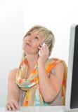 Donna senior dei bei capelli biondi che lavora all'ufficio con il telefono a Fotografia Stock Libera da Diritti