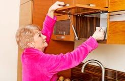 Donna senior di sorriso che prende tazza da un armadio da cucina fotografie stock libere da diritti
