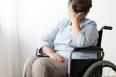 Donna senior disabile triste in un wheelchar fotografie stock