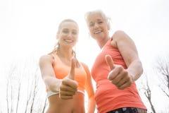Donna senior e figlia che danno i pollici su per lo sport fotografia stock