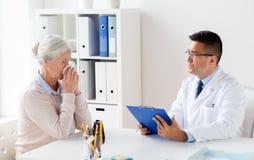 Donna senior e riunione di medico all'ospedale Immagine Stock