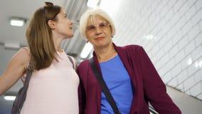 Donna senior e sua figlia sulla scala mobile in sottopassaggio Conversazione della figlia e della madre Famiglia felice che gode  stock footage