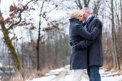 Donna senior ed uomo che si abbracciano nell'inverno Fotografie Stock