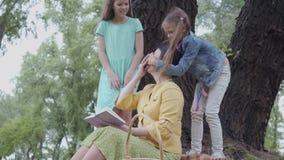 Donna senior elegante sveglia che si siede sulla coperta sotto l'albero nel parco che legge il libro Due nipoti sveglie stock footage