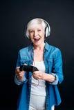 Donna senior esultata che gioca i video giochi Immagine Stock Libera da Diritti