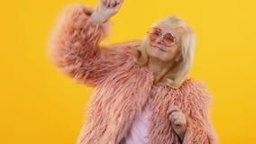 Donna senior felice che balla sul movimento lento giallo del fondo, giovane partito ritenente stock footage