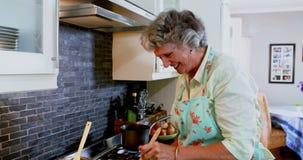 Donna senior felice che cucina alimento in cucina 4k archivi video