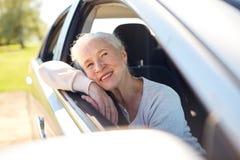 Donna senior felice che guida in automobile con la finestra aperta immagini stock libere da diritti