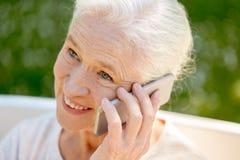 Donna senior felice che rivolge allo smartphone di estate Fotografia Stock Libera da Diritti