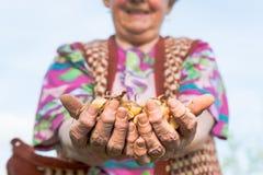 Donna senior felice che tiene fiero le cipolle del bambino Immagine Stock