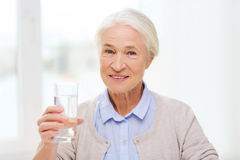 Donna senior felice con bicchiere d'acqua a casa Immagini Stock