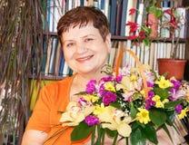 Donna senior felice con il canestro dei fiori fotografie stock