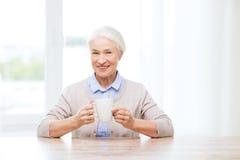 Donna senior felice con la tazza di tè o di caffè Fotografia Stock Libera da Diritti