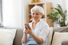 Donna senior felice con lo smartphone a casa fotografia stock