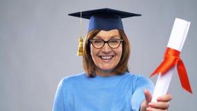 Donna senior felice del dottorando con il diploma video d archivio