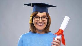 Donna senior felice del dottorando con il diploma archivi video
