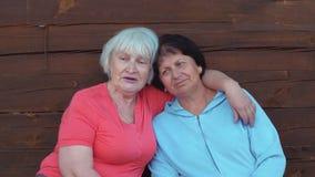 Donna senior felice due che abbraccia e allegramente che parla macchina fotografica anteriore video d archivio