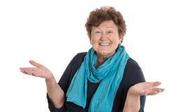 Donna senior felice isolata che porta sciarpa blu che presenta con la h immagine stock libera da diritti