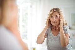 Donna senior frustrata che esamina specchio fotografie stock