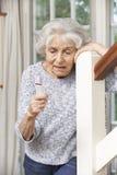 Donna senior indisposta che usando allarme personale a casa Immagini Stock