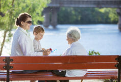 Donna senior, la sua nipote adulta e pronipote in parco Immagini Stock