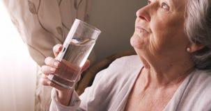 Donna senior malata che prende le pillole con acqua archivi video