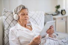 Donna senior malata con le cuffie e la compressa che si trovano a letto a casa o in ospedale fotografia stock