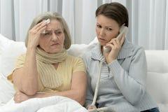 Donna senior malata e figlia preoccupata immagine stock