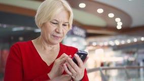 Donna senior nel sorridere del centro commerciale Facendo uso del suo smartphone, passando in rassegna, leggendo le notizie, chia video d archivio