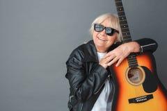 Donna senior nella condizione dello studio degli occhiali da sole e del bomber sul sogno abbracciante grigio della chitarra alleg immagini stock libere da diritti