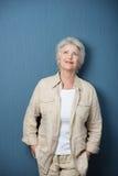 Donna senior nostalgica che porta camicia casuale beige Immagini Stock