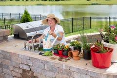 Donna senior pensionata che fa il giardinaggio, in un patio del mattone Immagine Stock