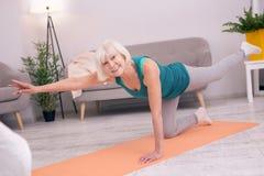 Donna senior piacevole che sta su su un ginocchio ed allungamento Fotografia Stock