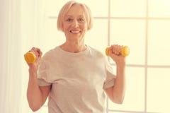 Donna senior positiva che si esercita con le teste di legno a casa Fotografia Stock
