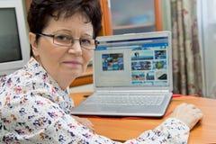 Donna senior positiva che si siede al taccuino e che guarda le immagini sui siti di viaggio Immagini Stock
